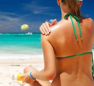 kobieta na plaży smarujaca się olejkiem do opalania by zachować naturalna opaleniznę