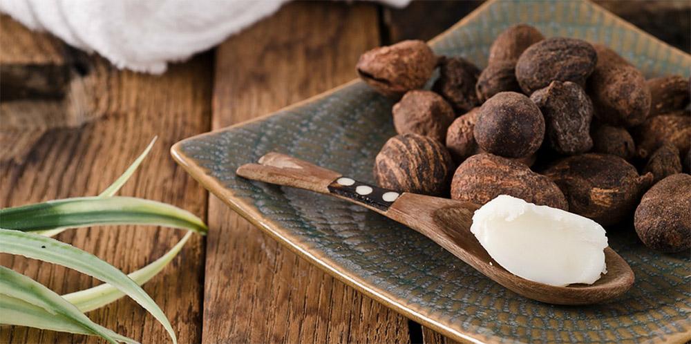masło shea  w kosmetyce -  nasiona masłosza i łyżeczka masła shea nierafinowanego