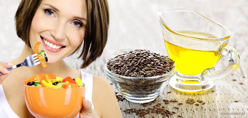 młoda kobieta na diecie dr Budwig je sałatkę z olejem lnianym, obok siemie lniane w miseczce i i olej lniany w pięknej szklanej buteleczce