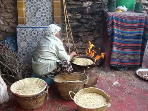 Marokańska kobieta przy palenisku, obok pojemniki z orzechami Arganii